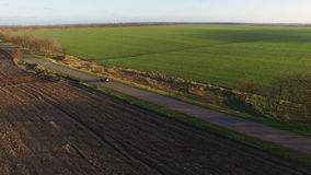 Aerial view of black car moving on the road countryside sunset green fields. Aerial view of black car moving the road countryside sunset green fields stock video