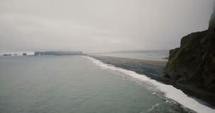Aerial view of the black volcanic beach in foggy day. Crowd of tourists walking on the ash shore of the sea. stock footage