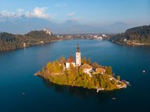 Aerial view of Bled island on lake Bled, and Bled castle and mountains in background, Slovenia. stock photo