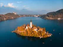 Aerial view of Bled island on lake Bled, and Bled castle and mountains in background, Slovenia. stock photos