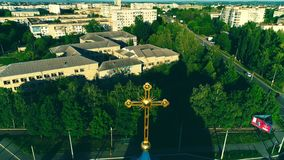 Drone aerial view of large residential district and church dome with golden cross. Aerial view of blessing church`s dome with large cross in the centre. Copy stock footage