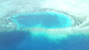 Aerial View of Blue Hole in Wakatobi National Park. Aerial view of a coral reef and blue hole in Wakatobi National Park in Indonesia. This region harbors stock video footage