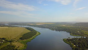 Aerial view of blue river with small village and fields on banks, drone shot of rural summer landscape stock footage