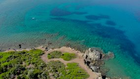 Aerial view of blue sea surface on rocky coast with light reflections. Top view of transparent turquoise ocean water surface and r. Ocks on shore stock footage