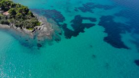 Aerial view of blue sea surface on rocky coast with light reflections. Top view of transparent turquoise ocean water surface and r. Ocks on shore stock video footage