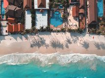 Aerial view of blue sea waves crushing against the sandy coast line, people enjoy summer near resorts and hotel line. Drone shot of blue sea waves crushing royalty free stock image