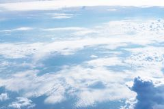 Aerial view of the blue skies and horizon with fluffy clouds and the earth below. royalty free stock photography