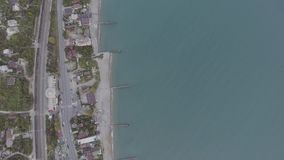Aerial view of blue water with harbour, town houses, rural road and cars. stock video footage