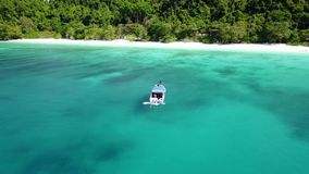 Aerial view of a boat on beautiful ocean with camera circle around stock footage