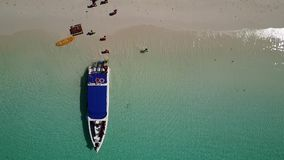 Aerial view of a boat disembark tourists on a beautiful beach stock video