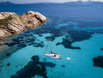 Aerial view of a boat in front of the Mortorio island in Sardinia. Amazing beach with a turquoise and transparent sea. Emerald Coa Stock Photo