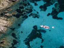 Aerial view of a boat in front of the Mortorio island in Sardinia. Amazing beach with a turquoise and transparent sea. Emerald Coa Stock Images