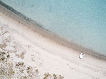 Aerial view of a boat in front of the Mortorio island in Sardinia. Amazing beach with a turquoise and transparent sea. Emerald Coa Stock Photography