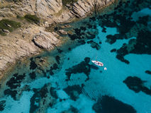 Aerial view of a boat in front of the Mortorio island in Sardinia. Amazing beach with a turquoise and transparent sea. Emerald Coa Royalty Free Stock Images