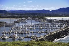 Aerial view of boat harbour. Aerial view of a harbour with boats moored and looking to mountains Stock Image