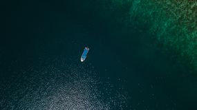 Aerial view of a boat next to a reef in the middle of the sea royalty free stock photography