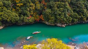 Aerial view boat on the river bring tourist people to enjoy autumn colors along katsura river to Arashiyama mountain area during. Fall season in Arashiyama royalty free stock photos