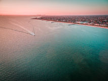 Aerial view of boat sailing across Port Phillip bay with Melbour. Ne coastline and suburban areas in the background at beautiful sunset Stock Photo