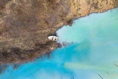 Aerial view of a boat in a turquoise lake contaminated with cyanide. Aerial drone view of a boat in a turquoise lake contaminated with cyanide mining residuals stock images