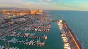 Aerial view of boats in the harbor, with city buildings behind stock footage