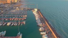 Aerial view of boats in the harbor, with city buildings behind stock video footage