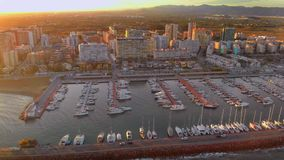 Aerial view of boats in the harbor, with city buildings behind stock video