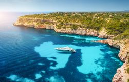 Aerial view of boats, luxury yachts and transparent sea at sunset. Aerial view of white luxury yacht and transparent sea at sunset in Mallorca, Spain. Colorful stock photography