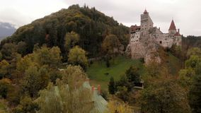 Aerial view of Bran castle in Romania. Aerial view of Bran castle in beautiful Transylvania, region of Romania. Cloudy autumn day with dark clouds stock video footage