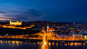 Aerial view of Bratislava, Slovakia at night. Famous castle and illuminated historical buildings with car traffic and river Stock Image