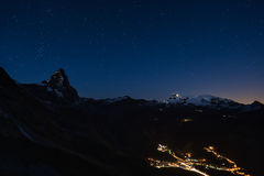 Aerial view of Breuil Cervinia village glowing in the night, famous ski resort in Aosta Valley, Italy. Wonderful starry sky over M Stock Photos