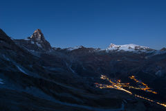 Aerial view of Breuil Cervinia village glowing in the night, famous ski resort in Aosta Valley, Italy. Wonderful starry sky over M Stock Photography