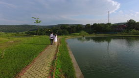 Aerial view of bride and groom walking along a lake on wedding day. Happy newlywed couple wearing traditional suits stock video