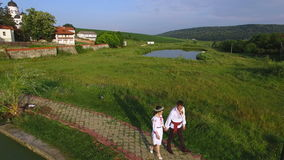 Aerial view of bride and groom walking along a lake on wedding day. Happy newlywed couple wearing traditional suits stock footage