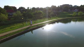 Aerial view of bride and groom walking along a lake on wedding day. Happy newlywed couple wearing traditional suits stock video footage