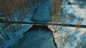 Aerial view on bridge across frozen lake at winter forest drone footage. 4K UHD stock footage
