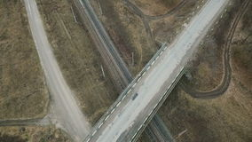 Aerial view: bridge with car, track, fields in the village stock footage