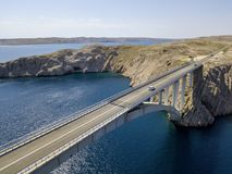 Aerial view of the bridge of the island of Pag, Croatia, roads and Croatian coast. Cliff overlooking the sea. Cars crossing the bridge seen from above royalty free stock images