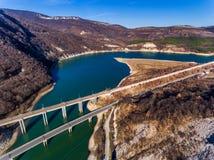 Aerial view of Bridge road near lake in mountain landscape Stock Photos