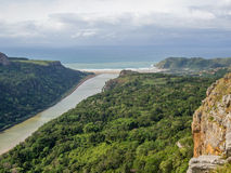 Aerial view of brown river surrounded by forest flowing into ocean at South Africa`s Wild Coast. Dramatic sky and beach in background Stock Photography