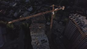 Aerial view of building cranes and buildings under construction. Fight over the construction site in the evening time stock footage