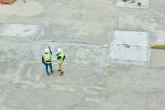 Aerial view of building inspectors. Drone view of two unrecognizable men in helmets and waistcoats inspecting construction site together Royalty Free Stock Photography