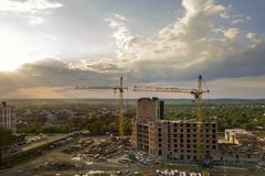 Aerial view of building site. Apartment or office building under construction. Tower cranes on suburb landscape and blue sky copy. Space background stock image