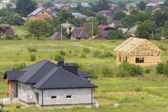 Aerial view of building site in green field. New brick house and wooden cottage under construction on village background. Property. Investment, professional stock photos
