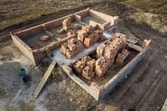 Aerial view of building site. Trenches dug in ground and filled with cement as foundation for future house, brick basement floor. And stacks of brick for royalty free stock images