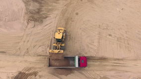 Aerial view of bulldozer pouring sand into truck stock video