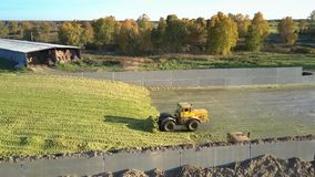 Aerial view bulldozers rake up silage on large pit heap. Aerial view bulldozers rake up harvested silage on large pit heap by hangar for agricultural machinery stock footage