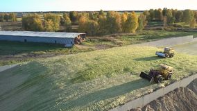 Aerial view bulldozers tamp silage on huge pit heap. Beautiful aerial view bulldozers tamp harvested silage on huge pit heap by hangar for machinery near trees stock video footage