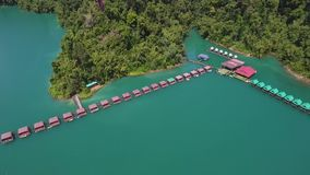 Aerial view on bungalows at Cheow Lan Lake, Khao Sok National Park in southern Thailand. HD Slowmotion. Aerial View on Bungalows at Cheow Lan Lake, Khao Sok stock footage
