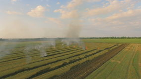 Aerial view of a burning field, outside a city, the air is filled with smoke stock video