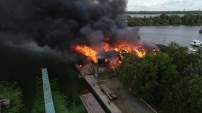 Aerial view of burnt industrial warehouse center building after big fire with huge smoke from burned roof